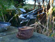 Bird sculpture made from up-cycled cutlery mounted on a log